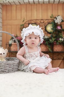 Free Baby Wearing White Headband And White Lace Floral Dress Sitting Beside Gray Wicker Basket Royalty Free Stock Photography - 92133817