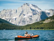 Free Person Riding On Black And Orange Boat Near Mountain Under White Clouds During Daytime Royalty Free Stock Image - 92160216
