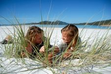 Two Young Girls Hiding Behind Grass On Beach Stock Image