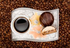 Coffee Cup With Sweets On Beans Background Stock Photo