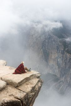 Free Person In Red And Black Blanket Sitting On Cliff Stock Photo - 92430090