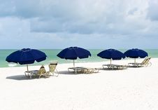 Lounge Chairs And Parasols On A Pristine White Sand Stock Photos
