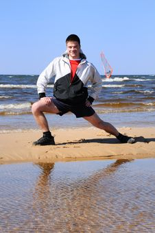 Young Man Doing Exercise At Beach Stock Photo