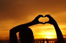 Free Silhouette Woman Hand Holding Heart Shape Against Orange Sky Royalty Free Stock Photo - 92753135