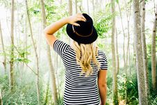 Free Woman Wearing Black Hat And Striped Shirt In Trees Touching Hat In Daytime Royalty Free Stock Photo - 92801585