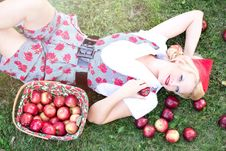Free Woman In Gray And White Rose Print Onesies Laying On Grass Beside Red Apple Fruits Royalty Free Stock Image - 92801716