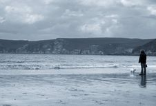 Free Lady Walking Her Dog On The Beach. Royalty Free Stock Image - 933036