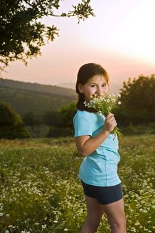 Girl Holding Flowers In Field At Sunset Stock Photography