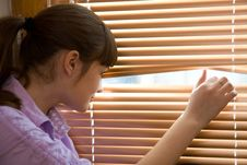 Teenager Girl Looks Out Of The Window Stock Image