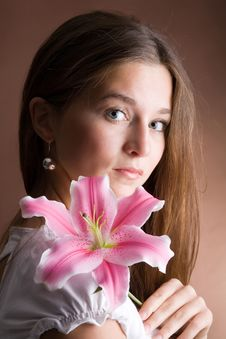 Free Young Woman Posing With A Pink Lily Royalty Free Stock Photo - 9340165