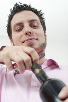 Young Man Opening A Bottle Of Red Wine Royalty Free Stock Photos