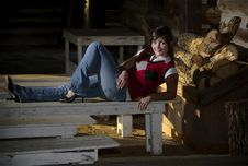 Teenager Relaxing On A Bench In A Rustic Cabin Stock Image