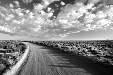 Free Grayscale Photo Of Empty Road Between Grass Field Under Cloudy Sky Royalty Free Stock Image - 93553996