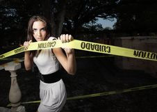 Woman Pulling On Caution Tape Stock Photo