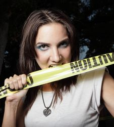 Woman Biting Caution Tape Stock Photo