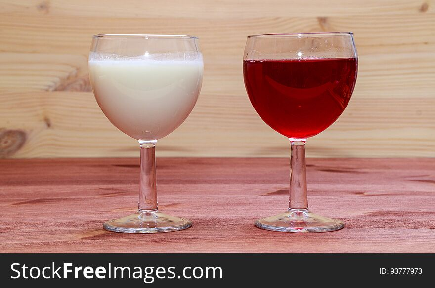 Glasses with wine and milk