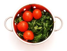 Arugula And Tomatoes In Stainless Steel Stainer