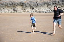 Free Father And Son Racing Along The Beach Royalty Free Stock Images - 9428689