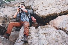 Free Man Sitting On Rock While Taking Pictures Stock Photos - 94243703