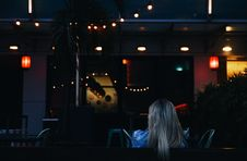 Free Blonde Woman Sitting Under String Lights At Night Stock Photography - 94243972