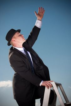 Free Man Reaching From Ladder Royalty Free Stock Photography - 9430517