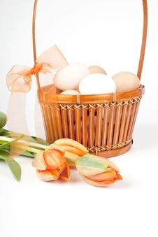 Eggs In A Basket And Tulips Stock Photo