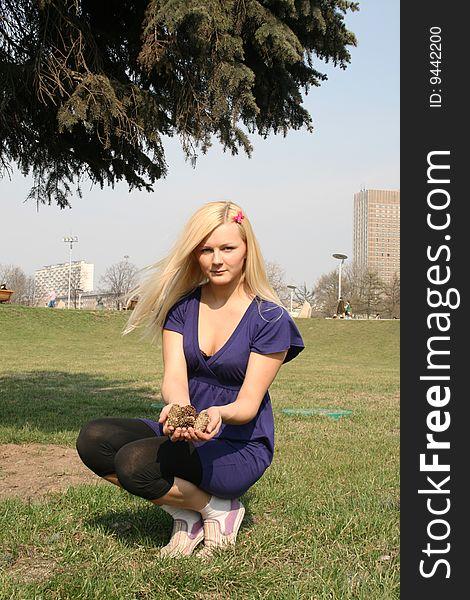 Girl sitting under fir tree
