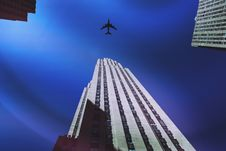 Free Plane Flying Over A Skyscraper Royalty Free Stock Image - 94484326