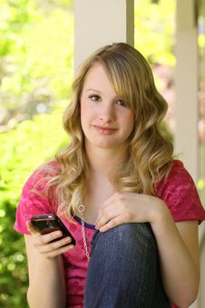 Attractive Teenager Sitting On Front Porch Stock Photo