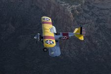 Free Yellow Biplane Over Large Canyon Stock Photo - 9452550