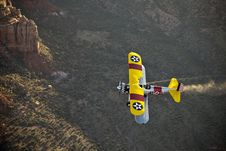 Free Yellow Biplane Over Desert Stock Photo - 9452590