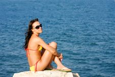 Girl Sits On The Beach Of The Blue Sea Royalty Free Stock Images