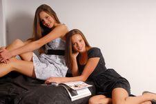 Free Two Beautiful Twin-girls Reading A Magazine Royalty Free Stock Photo - 9483845