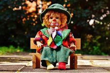 Free Clown Doll On Bench Outdoors Royalty Free Stock Images - 94945399
