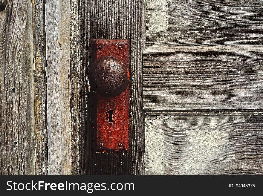 Rusty door knob on wooden door