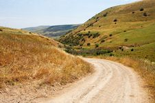 Free Countryside Road Bends Among Yellow Hills Royalty Free Stock Photography - 9539107