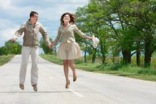 Free Couple Jumping On Rural Road Royalty Free Stock Image - 9544616