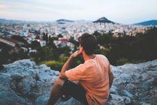 Free Man In Orange Shirt Sitting On Gray Rocks Stock Photo - 95537010
