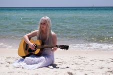 Free Blond Woman Playing Spruce Top Dreadnought Acoustic Guitar By The Seashore Stock Photo - 95593370