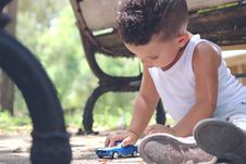 Free Boy In White Tank Top Playing Blue Coupe Die Cast Near Brown Wooden Bench Chair During Daytime Stock Photography - 95697662