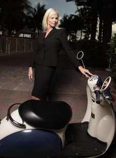 Businesswoman And A Motor Scooter Royalty Free Stock Photo