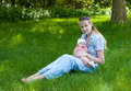 Free Baby And Mother Sitting In The Grass Stock Photos - 9599353