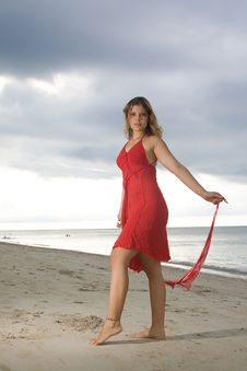 Free Girl With Red Dress Standing In The Sand Stock Photography - 9606782