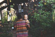 Free Woman In Orange Pink Aztec Dress Carrying Child In Orange Shirt Stock Photo - 96054880