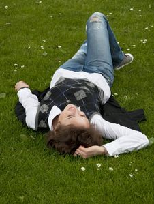 Student Girl Lays On The Grass Stock Photo