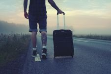 Free Man Walking On The Road Holding Black Luggage During Sunset Stock Photography - 96494632