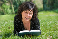 Free Smiling Girl Lying On A Meadow Reads A Book Stock Photo - 9659120