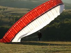 Free Man On The Ground With A Red Black And White Parachute Stock Image - 96542441