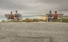 Free Two Couple Sitting On Bench Near Beach Stock Photography - 96580892
