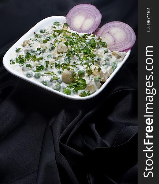 Pea Potato Salad on black background